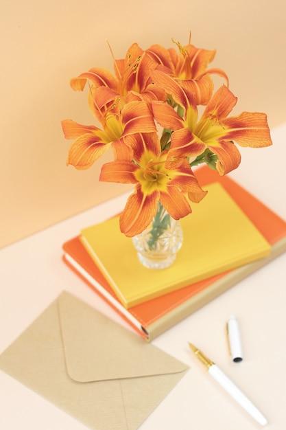 Orange zusammensetzung mit blumen und notizbüchern Premium Fotos