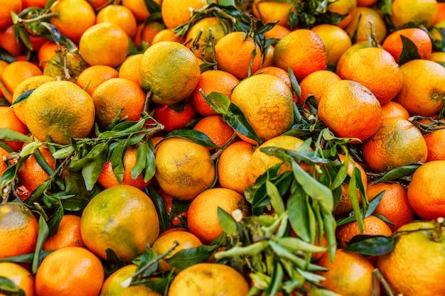 Orangen mit zweigen und blättern auf der theke. nahansicht. . copyspace. Premium Fotos