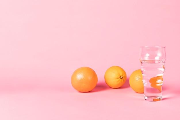 Orangen und glas wasser mit exemplarplatz Kostenlose Fotos