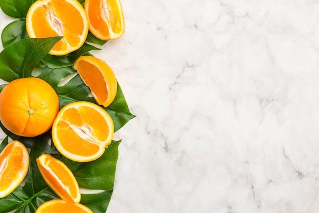 Orangen und monstera treiben auf marmoroberfläche blätter Kostenlose Fotos