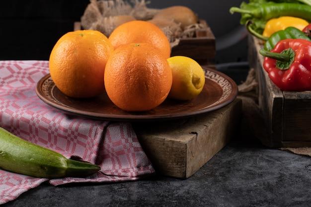 Orangen und zitrone auf einer platte auf einem stück stein. Kostenlose Fotos