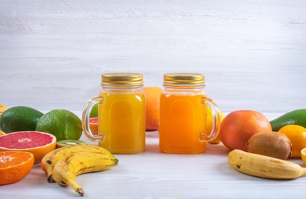 Orangen- und zitronensaft umgeben durch verschiedene bunte frische zitrusfrüchte auf weißer tabelle Kostenlose Fotos