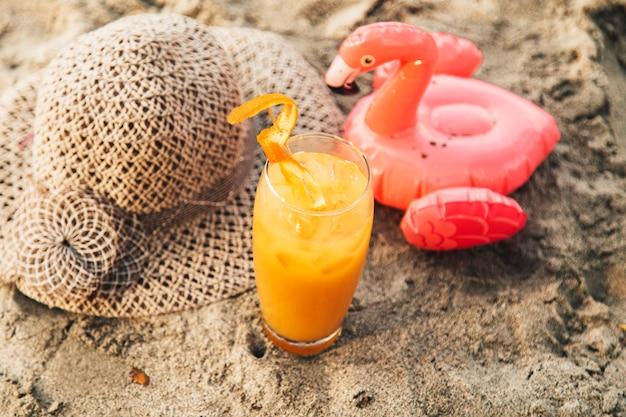 Orangencocktail auf sand Kostenlose Fotos