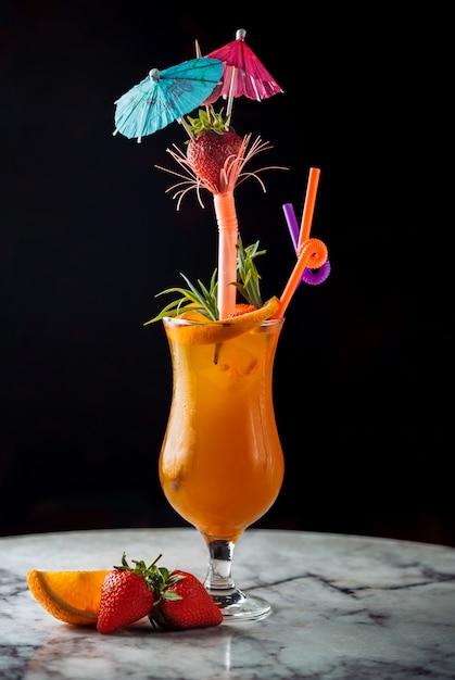 Orangencocktail des sommergetränks mit rohren und regenschirmen. Kostenlose Fotos