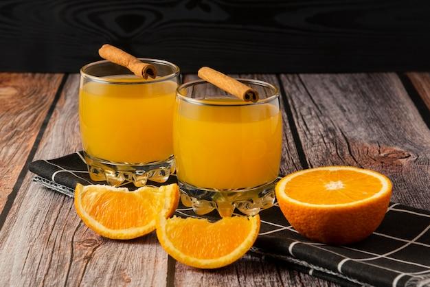 Orangenfrucht mit einem glas saft und zimtstangen Kostenlose Fotos