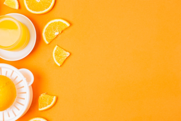 Orangensaft der flachen lage auf orange hintergrund mit kopienraum Kostenlose Fotos