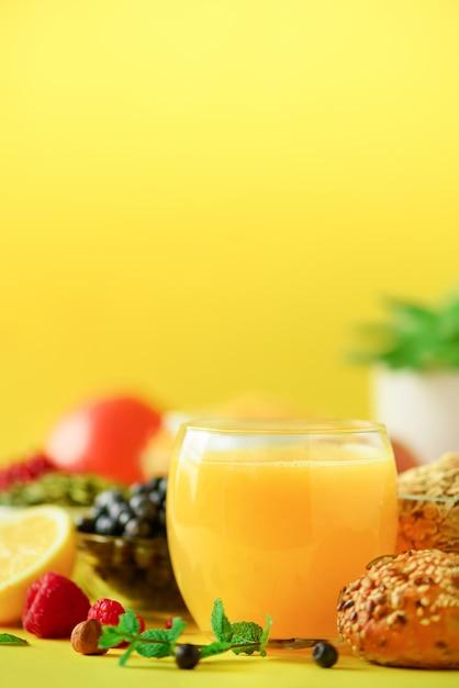Orangensaft, frische beeren, milch, joghurt, gekochtes ei, nüsse, früchte, banane, pfirsich zum frühstück. gesundes lebensmittelkonzept. Premium Fotos