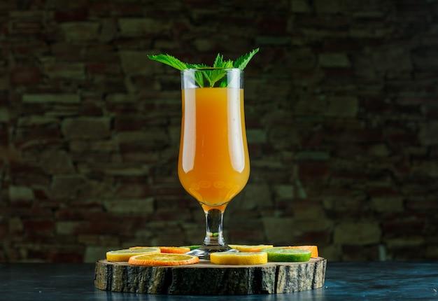 Orangensaft in einem becher mit minze, limette, zitrone, orange, holzbrett seitenansicht auf blauem und ziegelsteinhintergrund Kostenlose Fotos