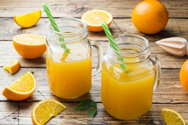 Orangensaft in glasgefäßen und frische orangen auf einem hölzernen rustikalen hintergrund. Premium Fotos