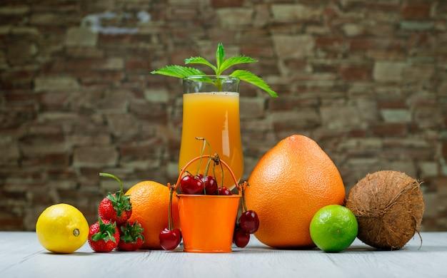 Orangensaft mit minze, orange, limette, zitrone, erdbeere, kirsche, kokosnuss, grapefruit in einem becher auf ziegelstein und holzoberfläche, seitenansicht. Kostenlose Fotos