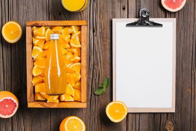 Orangensaft und klemmbrett topview auf hölzernem hintergrund Kostenlose Fotos