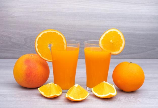 Orangensaft verziert durch ganzes und schnitt der frischen orange auf holzoberfläche Kostenlose Fotos