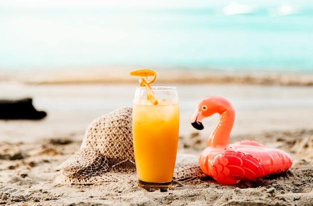 Orangensaftgetränk und spielzeugflamingo auf sand Kostenlose Fotos