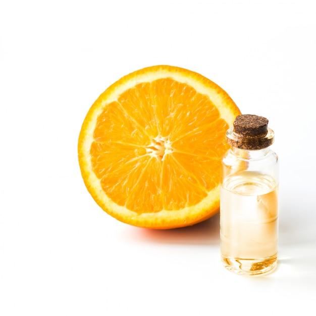 Orangenscheibe obst und flasche mit öl oder essenz. runde scheibe lokalisiert auf weiß. nahansicht. Premium Fotos