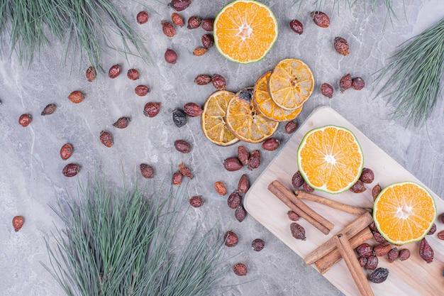 Orangenscheiben mit hüften und zimt auf einer holzplatte Kostenlose Fotos