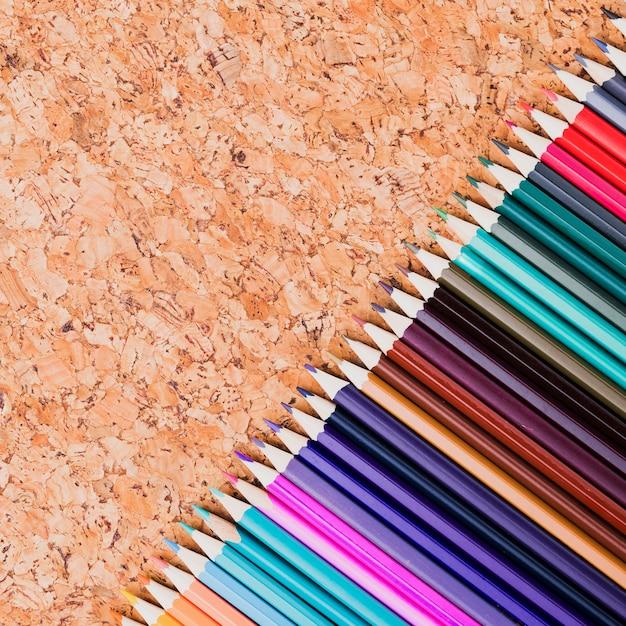 Ordentliche reihe der farbenbleistifte diagonal gesetzt auf korkenhintergrund Kostenlose Fotos