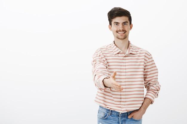 Ordentlicher höflicher mann, der neuen arbeitgeber grüßt. porträt eines gut aussehenden selbstbewussten, freundlichen männlichen models mit schnurrbart und bart, das im handschlag die hand in richtung zieht und den neuankömmling über der grauen wand begrüßt Kostenlose Fotos