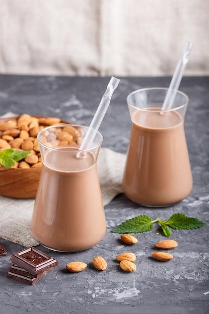 Organische nichtmilchmandel-schokoladenmilch in der glas- und holzplatte mit mandelnüssen auf einem schwarzen konkreten hintergrund Premium Fotos