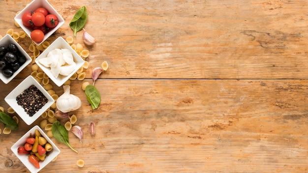 Organische rohe bestandteile mit conchiglie teigwaren auf braunem schreibtisch Kostenlose Fotos