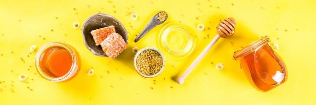 Organischer blumenhonig, in den gläsern, mit den blütenstaub- und honigkämmen, mit draufsichtkopienraum-fahnenformat der hellen gelben wand des kreativen plans der wildblumen Premium Fotos