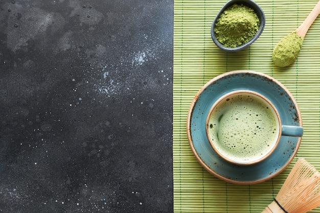 Organischer grüner matcha tee der zeremonie auf schwarzer tabelle. ansicht von oben. platz für text. Premium Fotos