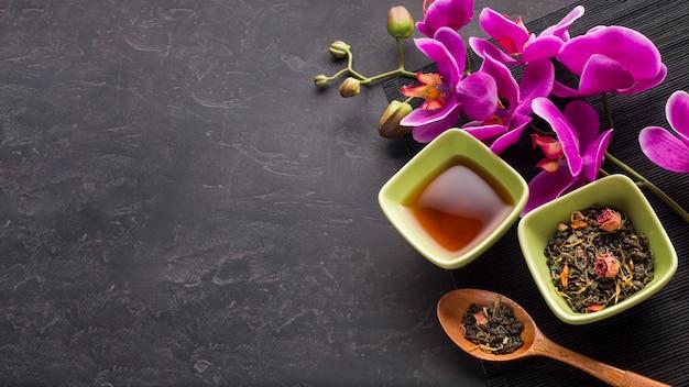 Organisches getrocknetes teekraut und rosa orchideenblume auf schwarzem hintergrund Kostenlose Fotos