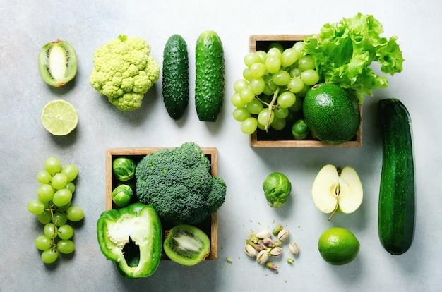 Organisches grünes gemüse und früchte auf grau. platz kopieren, flach legen, draufsicht. grüner apfel, salat, zucchini, gurke, avocado, grünkohl, limette, kiwi, trauben, bananen, brokkoli Premium Fotos