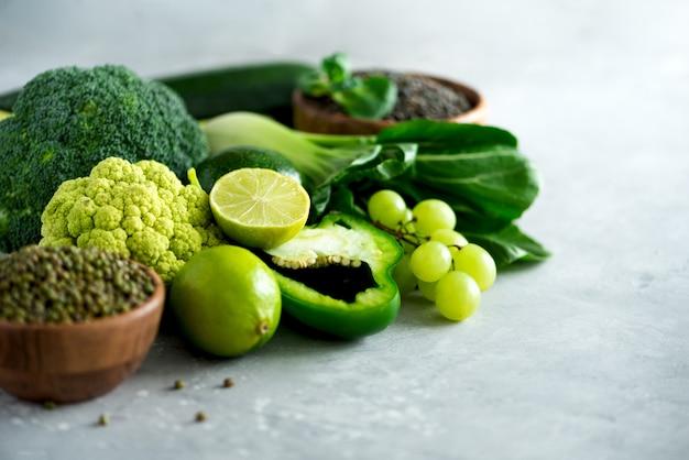Organisches grünes gemüse und früchte auf grauem hintergrund. Premium Fotos