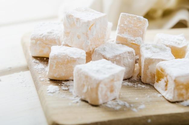 Orientalische bonbons im puderzucker auf hölzernem brett Premium Fotos