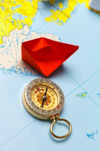 Origami papierschiff auf einer karte. führungs- und reisekonzept Premium Fotos