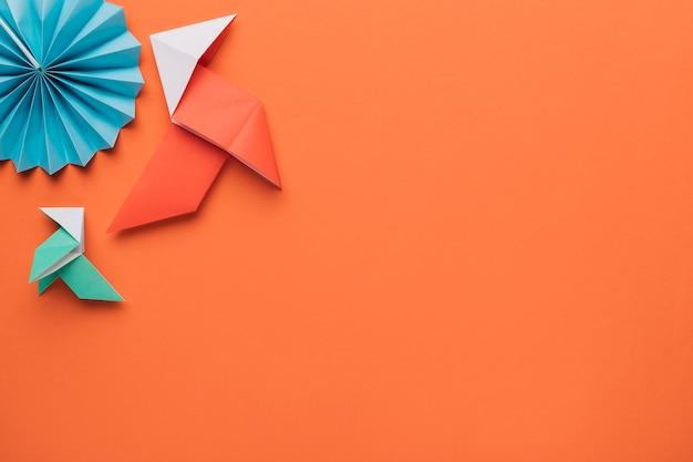 Origamipapierhandwerkskunst auf dunkelorangeer oberfläche Kostenlose Fotos