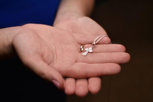 Orthodoxes kreuz in den händen einer frauenmutter während der taufe Premium Fotos