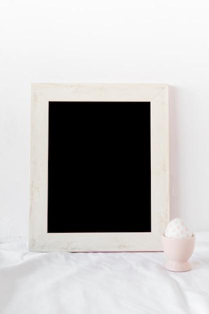 Osterei in der schale nahe fotorahmen auf gewebe Kostenlose Fotos