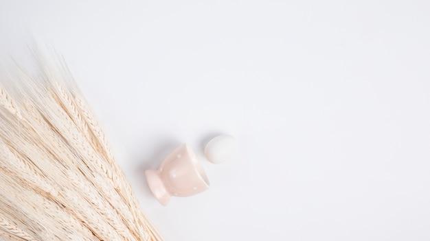 Osterei nahe schale und bündel frischem weizen Kostenlose Fotos