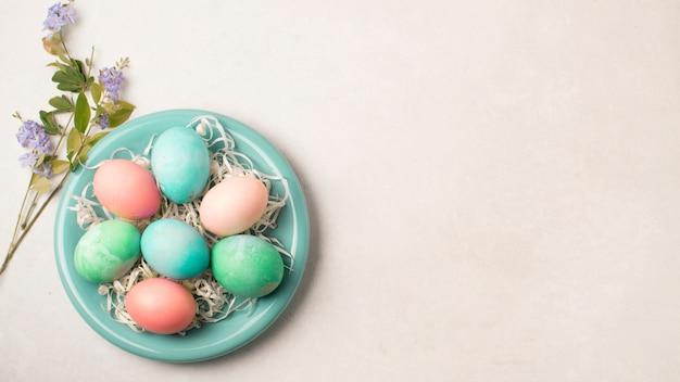 Ostereier auf platte nahe blumenzweigen Kostenlose Fotos