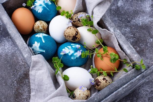 Ostereier aus natürlichem farbstoff bemalt und mit pflanzenblättern verziert Premium Fotos