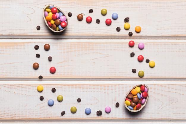 Ostereier füllten mit bunten süßigkeiten auf hölzernem schreibtisch mit raum in der mitte für das schreiben des textes Kostenlose Fotos