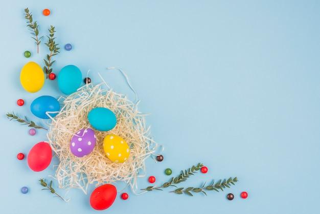 Ostereier im nest mit betriebsniederlassungen auf blauer tabelle Kostenlose Fotos