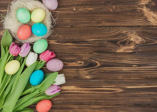 Ostereier im nest mit tulpen auf dem tisch Kostenlose Fotos