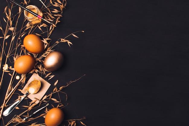 Ostereier in der nähe von löffel auf papier und pinsel auf farbstoff können zwischen trockenem gras Kostenlose Fotos