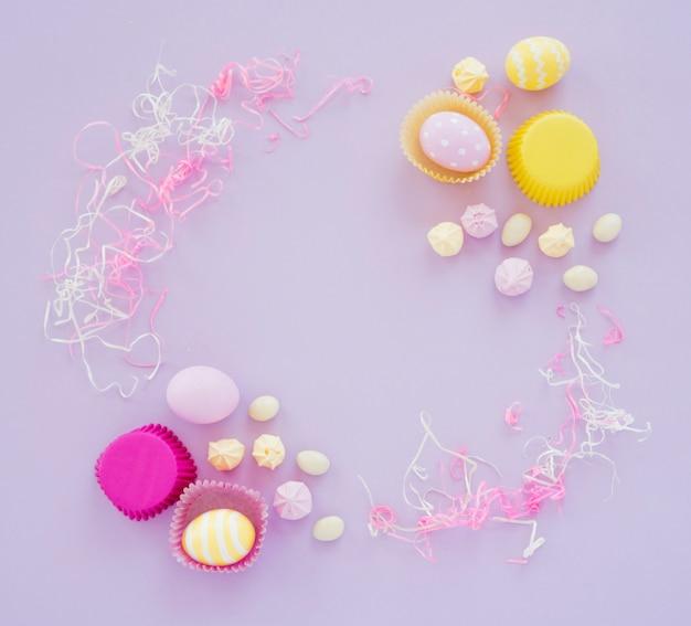 Ostereier mit bonbons auf purpurroter tabelle Kostenlose Fotos