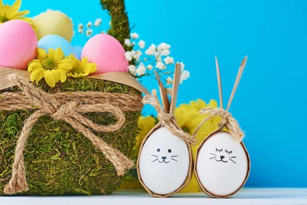 Ostereier mit gemalten gesichtern und dekorativem korb auf einem blauen bacground Premium Fotos