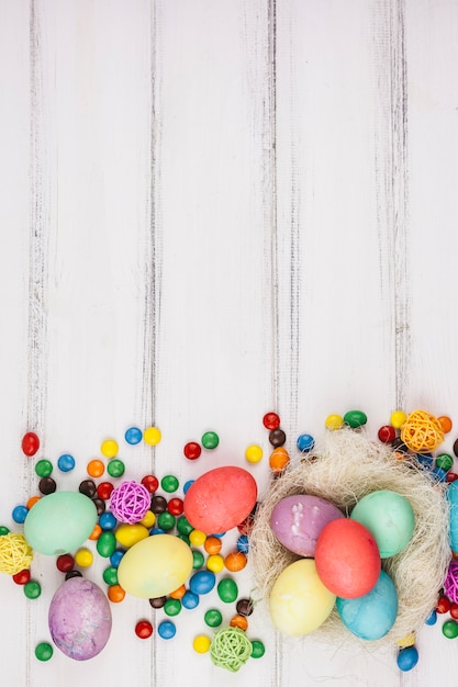 Ostereier mit kleinen süßigkeiten auf tabelle Kostenlose Fotos