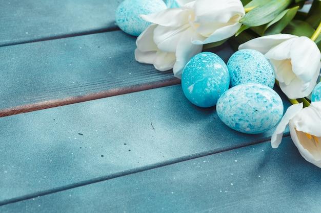 Ostereier mit tulpen auf blauem hölzernem hintergrund Premium Fotos