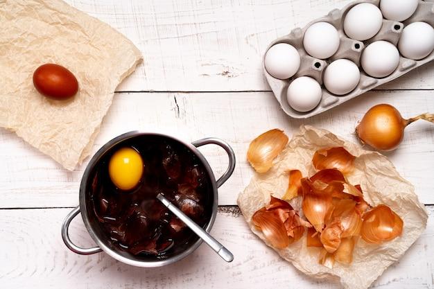 Ostereier, natürlicher farbfärbeprozess, zwiebelschalen in einem kleinen topf auf einem weißen hölzernen hintergrund. Premium Fotos