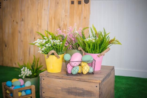 Ostereier und frühlingsblumen im korb, kasten auf holztisch Premium Fotos