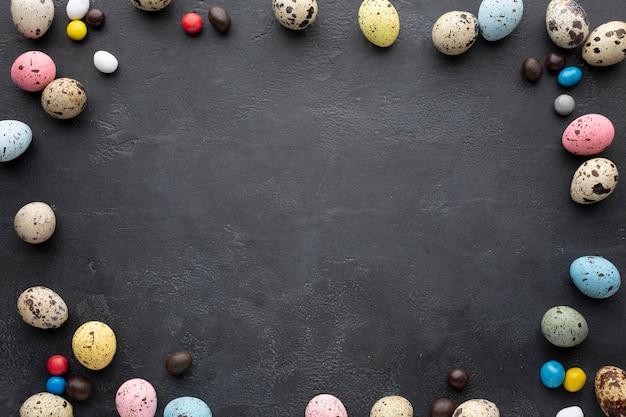 Ostereierrahmen mit süßigkeit auf schieferhintergrund Kostenlose Fotos