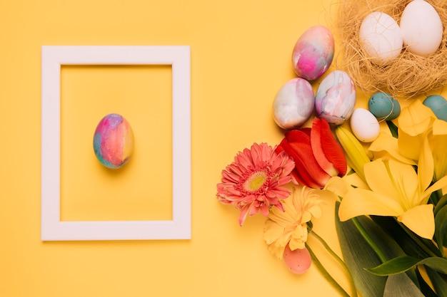Ostereiweiß-grenzrahmen mit frischen blumen und eiern nisten auf gelbem hintergrund Kostenlose Fotos