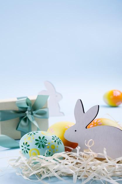 Osterferienhintergrund bunt bemalte hühnereier, weißer holzhase und geschenkbox mit band. osterferiendekorzusammensetzung Premium Fotos