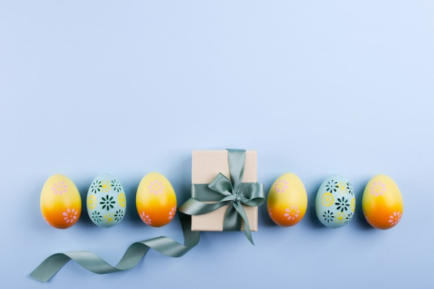 Osterferienhintergrund draufsicht von bunt bemalten hühnereiern, die in einer reihe und geschenkbox mit band plattiert werden Premium Fotos